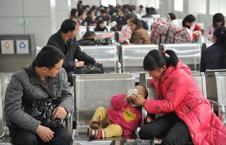 A family wait for their train in Guangzhou. Guangdong is expected to become the first province to generate GDP of 5 trillion yuan in one year. (File Photo/Xinhua)